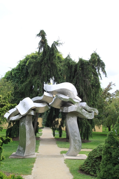 "This sculpture mirrors the shape of the evergreen behind. Grounds for Sculpture Hamilton NJ ""Sagg Portal"" Hans Van de Bovenkamp"