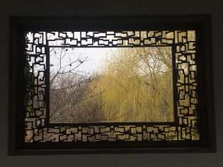 Leaky Window Frame framing the yellow of weeping willow.